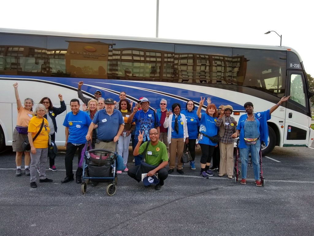 Group picture of Jane Addams Seniors in Action members posing in front of a bus.
