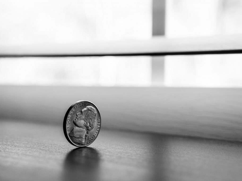 Picture of a coin balanced by a window