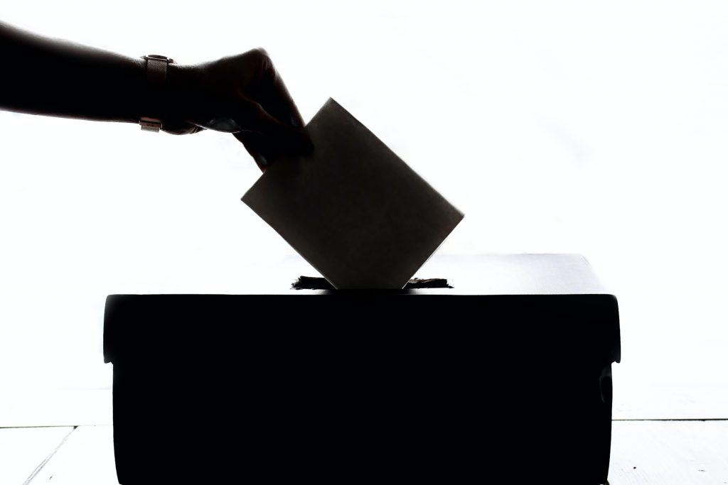 Picture of hand placing ballot in box.