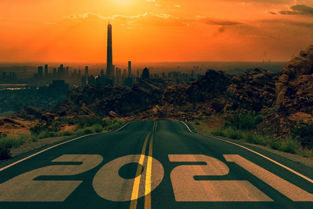 Photo of Road that has 2021 printed on it leading into a city at dusk.