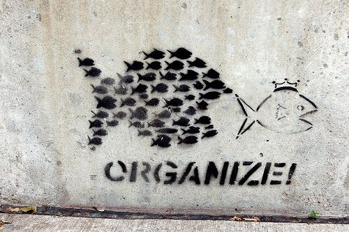 Art on wall showing a school of stylized fish about to eat a large fish with the word organize beneath it.