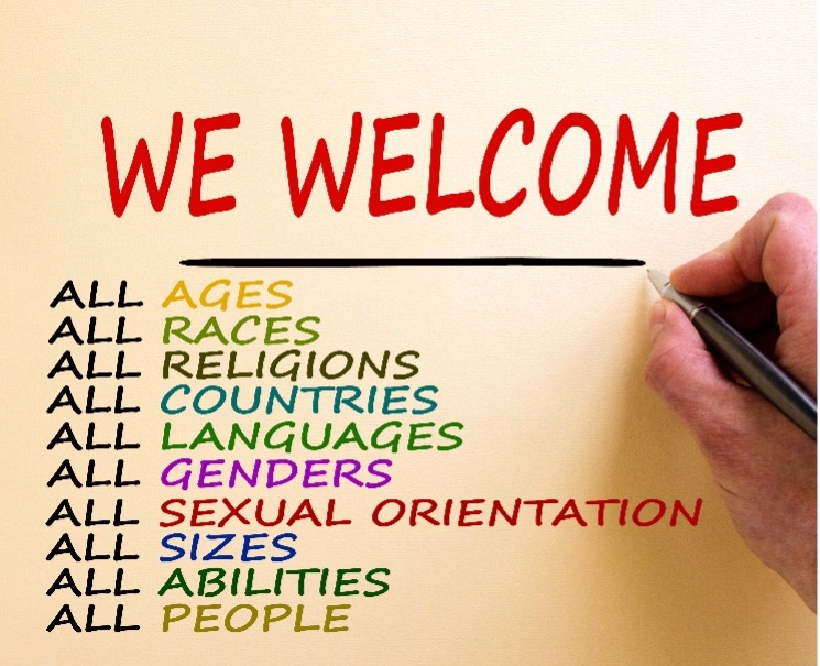 """Image Description: A hand on the right holding a pen to write: """"We welcome: all ages, all races, all religions, all countries, all languages, all genders, all sexual orientation, all sizes, all abilities, all people."""