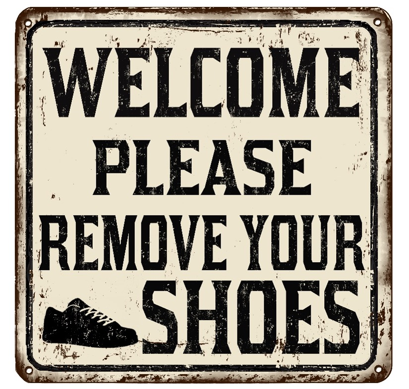"""Image Description: A faded, metallic sign with black lettering saying """"Welcome Please Remove Your Shoes"""" with a sneaker icon in the bottom left."""