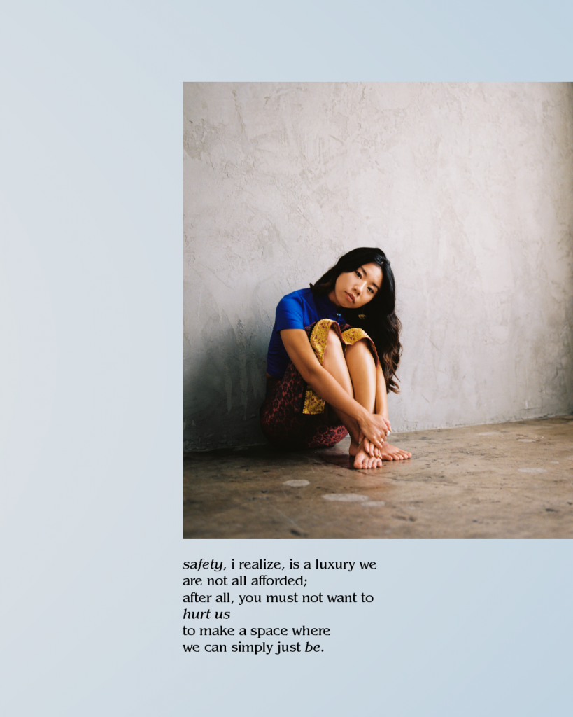 Image Description: A picture of an Asian American woman sitting against a gray wall. She is wearing a blue shirt and yellow skirt. Her head is tilted to the right and she is looking into the camera.