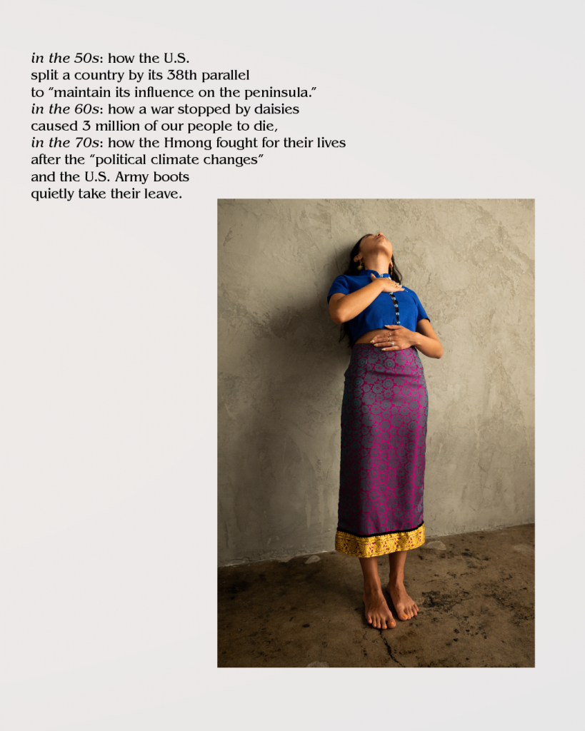 Image description: Image of Asian American women holding her stomach and chest leaning back against a gray wall and looking up. She is wearing a blue shirt and long purple skirt with no shoes.