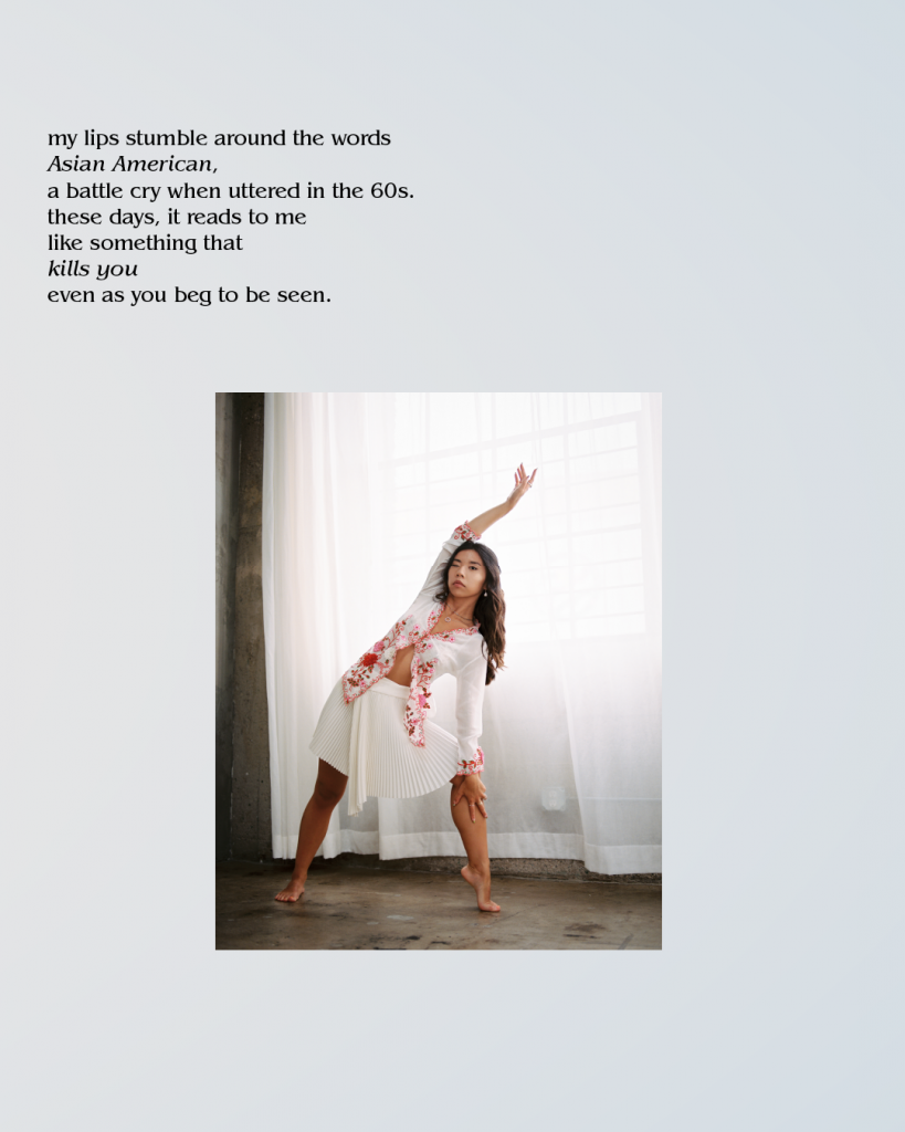 Image Description: An Asian American woman wearing a loose fitting white and red shirt and skirt. She is stretching her arm over her head and leaning to the right. The background is room that has white windows covered by a large white/sheer curtain.