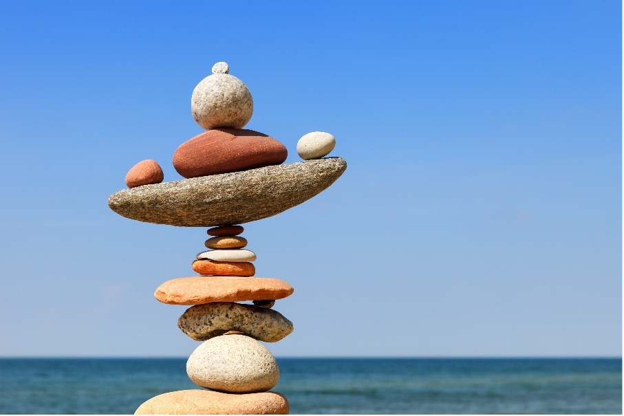 Image description: Rocks balanced on one another with the ocean in the background.