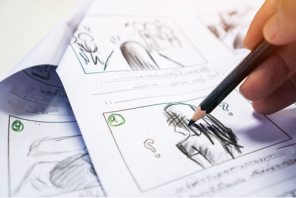 Image Description: A hand holds a pencil on the right side of a storyboard, hovering over a drawing of a person with question marks around their head.