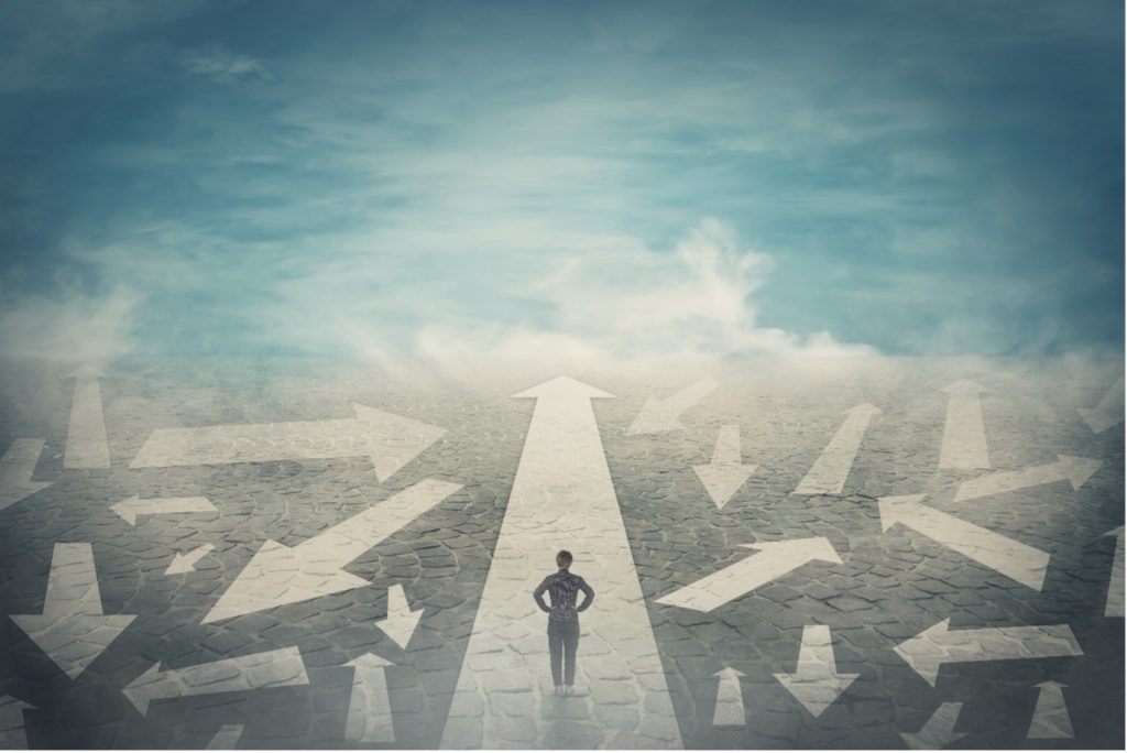 Image Description: A person stands with hands on hips at the start of a path pointing straight ahead. The background is gray-blue and cloudy, with many arrows pointing in all directions on the sides. Image by StunningArt on Shutterstock