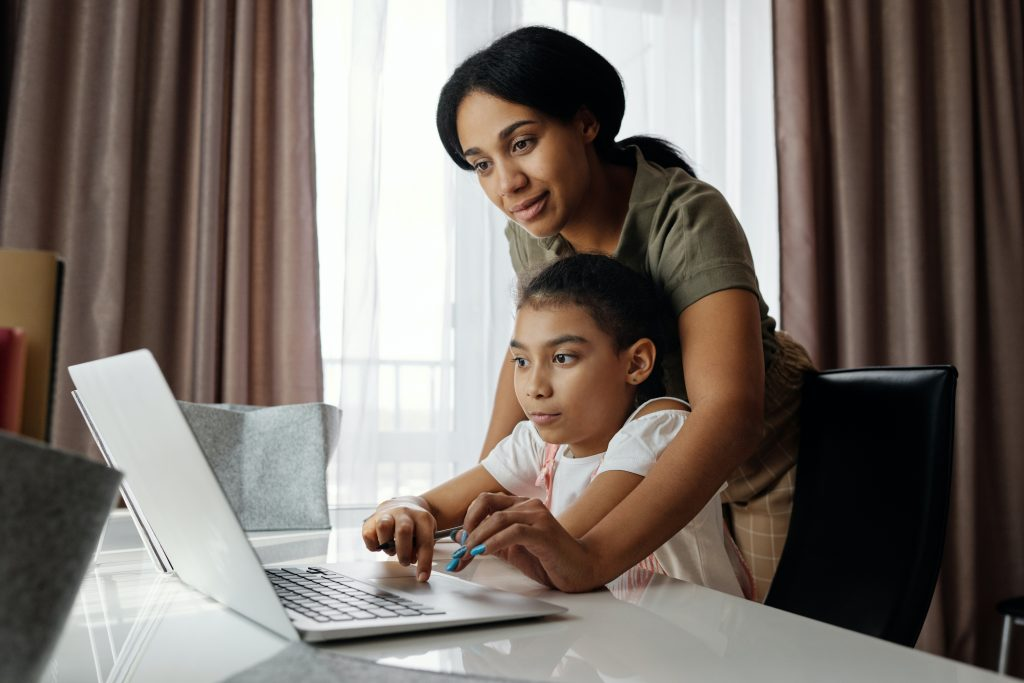 Image Description: A Picture of a mother helping her daughter do homework at a laptop.